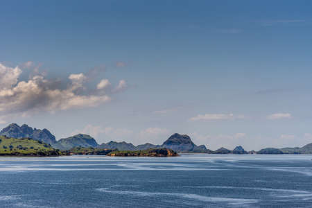 Komodo Island, Indonesia - February 24, 2019: Green hills under blue sky with cloudscape, part of Komodo National Park. Islets in blue sea. Stock Photo