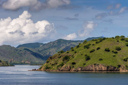 Komodo Island, Indonesia - February 24, 2019: Green mountains descending into sea water under blue sky with cloudscape, part of Komodo National Park. Stock Photo