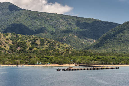 Komodo Island, Indonesia - February 24, 2019: Pier of Komodo National Park in blue sea. Green forested hills in back under blue sky with white clouds. Strip of sandy beach with small boats in surf.