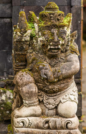 Bali, Indonesia - February 25, 2019: Ulun Danu Beratan Temple complex in Bedoegoel. Green moss and black mold covers gray stone statue of small man with funny face.