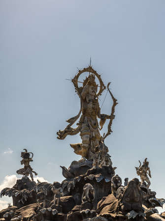 Denpasar, Bali, Indonesia - February 26, 2019: Closeup of Patung Titi Banda brown stone statue of holy warrior in center of roundabout of By Pass Ngurah Rai Street under light blue sky.