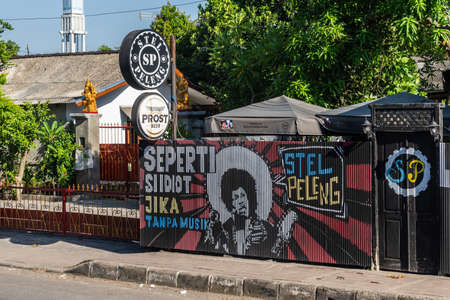 Denpasar, Bali, Indonesia - February 26, 2019: Stel Peleng restaurant, bar and dance club facade along Ji. Prof. Dr. Ida Bagus Mantra. Colorful music themed wall painting and green foliage.