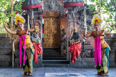 Banjar Gelulung, Bali, Indonesia - February 26, 2019: Mas Village. Play on stage setting. Two women with head ornaments and traditional dress with pink garlands dance.