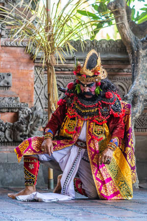 Banjar Gelulung, Bali, Indonesia - February 26, 2019: Mas Village. Play on stage setting. Closeup of in submission kneeling King in decorated garb of reds, golds, yellow, and blacks. Green foliage.
