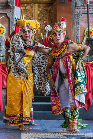 Banjar Gelulung, Bali, Indonesia - February 26, 2019: Mas Village. Play on stage setting. Closeup of two Queens in traditional garb with golds, blacks, white and reds in front of temple entrance. Editorial