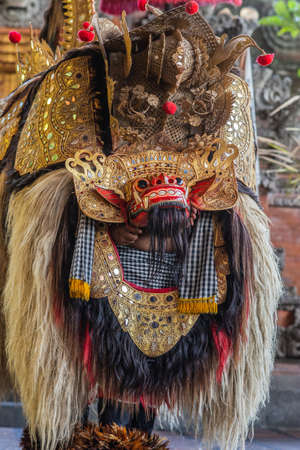 Banjar Gelulung, Bali, Indonesia - February 26, 2019: Mas Village. Play on stage setting. Closeup of dragon with mask and long blond hair standing on stage, front down, back up. Lots of reds, golds and browns.