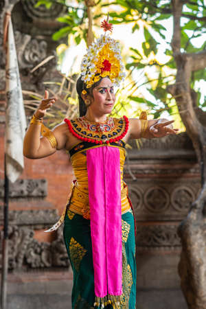 Banjar Gelulung, Bali, Indonesia - February 26, 2019: Mas Village. Play on stage setting. Closeup of female dancer with elaborate flower head piece, traditional garb with pinks, golds, blues and reds.