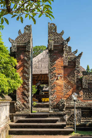 Ubud, Bali, Indonesia - February 26, 2019: Batuan Temple. Smaller Split gate separates two mandalas, courtyards under blye sky and with green foliage. Banco de Imagens