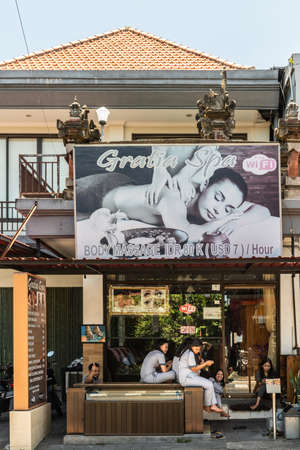 Ubud, Bali, Indonesia - February 26, 2019: Downtown Pedang Tegal, Ji. Hanoman street, commercial district. Closeup of front of Gratia Spa and Massage Parlor. Upper level hidden by large photo-billboard. Group of masseuses sitting and waiting at street.