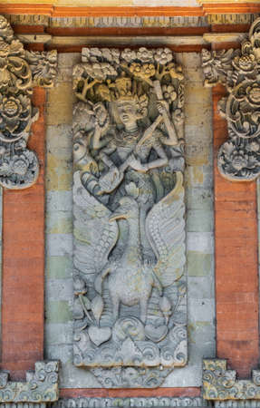 Ubud, Bali, Indonesia - February 26, 2019: Batuan Temple. Devi Saraswati mural shows woman playing musical instrument, swan and flowers in gray stone against red brick wall.