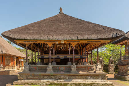 Ubud, Bali, Indonesia - February 26, 2019: Batuan Temple. Large open shrine with reed roof set on green lawn under blue sky. White stone statues and gold decorations. 免版税图像