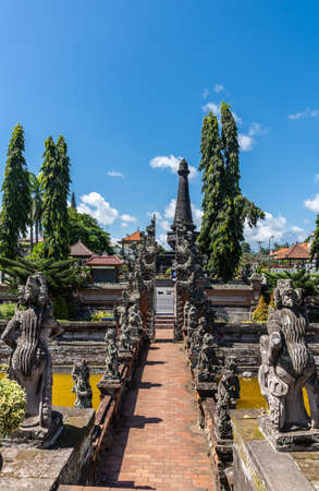 Klungkung, Bali, Indonesia - February 26, 2019: looking from floating pavilion towards street, over bridge over lotus pond and collection of gray stone statues, split gate, under blue sky. Green trees and Puputan Klungkung Monument tower. Green trees.