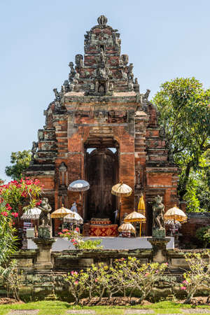 Klungkung, Bali, Indonesia - February 26, 2019: Closeup of Red brick and gray stone ornaments of door and gate, now in ruin, to disappeared historic Royal Palace under blue sky, set in green garden with colors added by flowers and umbrellas.