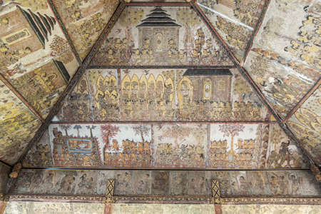 Klungkung, Bali, Indonesia - February 26, 2019: Kertha Gosa, Open sides Royal Court of Justice, ceiling full of paintings about punishments and rewards. Brown beams and lots of gold