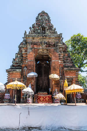 Klungkung, Bali, Indonesia - February 26, 2019: Closeup of Red brick and gray stone ornaments of door and gate, now in ruin, to disappeared historic Royal Palace under blue sky, colors added by umbrellas.