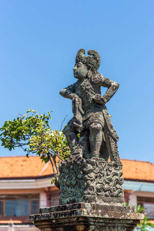 Klungkung, Bali, Indonesia - February 26, 2019: Closeup of Stone statue of defiant King covered in black mold against blue sky. Some green foliage and red roof. Stock Photo