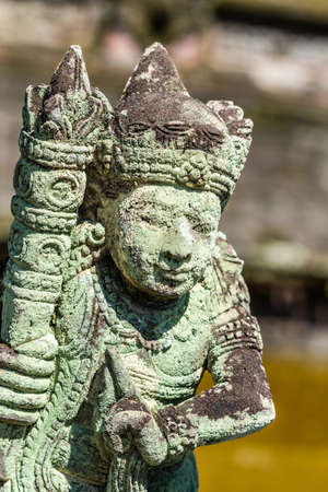 Klungkung, Bali, Indonesia - February 26, 2019: Closeup of Stone statue of person with club, totally covered in green and black mold.