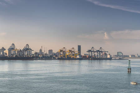 Makassar, Sulawesi, Indonesia - February 28, 2019: Early morning sky over container harbor shows three ships and many cranes with city buildings on horizon. Banco de Imagens