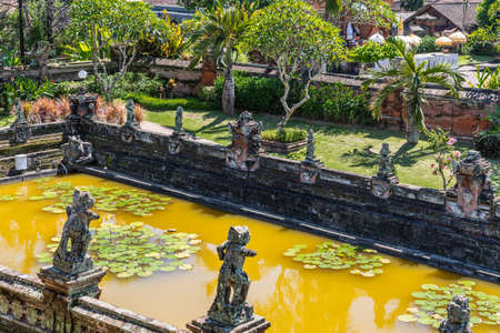 Klungkung, Bali, Indonesia - February 26, 2019: Lotus pond seen from Floating Pavilion at Royal Palace comes with turmeric-colored water, green plants, and is bordered by a collection of gray stone statues. Green foliage in back. Editorial