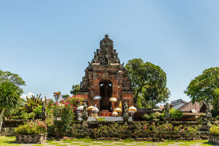 Klungkung, Bali, Indonesia - February 26, 2019: Red brick and gray stone ornaments of door and gate, now in ruin, to disappeared historic Royal Palace under blue sky, set in green garden with colors added by flowers.