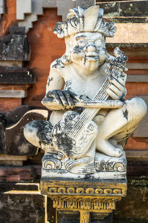 Klungkung, Bali, Indonesia - February 26, 2019: Closeup of white statue of violin player at Royal Palace. Black mold on statue and stone behind of red bricks. Editorial