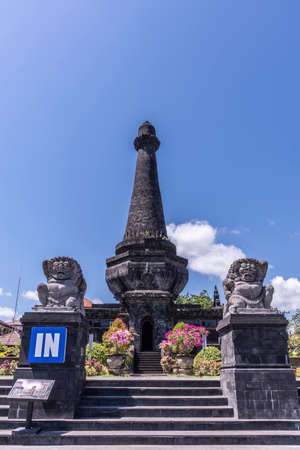 Klungkung, Bali, Indonesia - February 26, 2019: Black Oblisk Puputan Monument remembering a suicidal royal battle against invaders under blue sky. Phallus symbol and two lion statues as guards. Pink flowers set in green.
