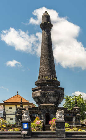 Klungkung, Bali, Indonesia - February 26, 2019: Black Oblisk Puputan Monument remembering a suicidal royal battle against invaders under blue sky. Phallus symbol and two lion statues as guards. Pink flowers set in green. Building in back.