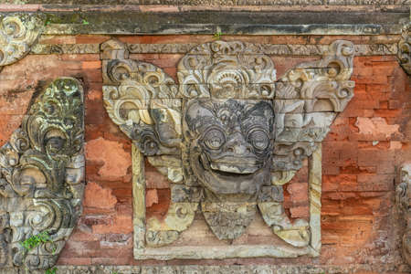 Klungkung, Bali, Indonesia - February 26, 2019: Royal Palace. Closeup of gray stone mask mural set in red brick wall.