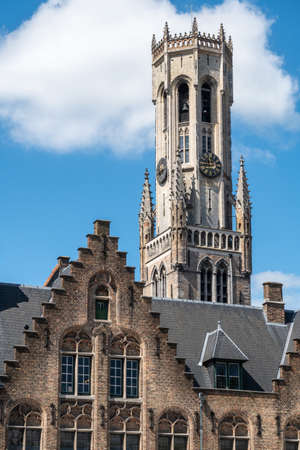 Bruges, Flanders, Belgium -  June 17, 2019: Gray stone tower of Belfry with clock peeps over brown brick step gable under blue sky with whtie cloud. Stock Photo