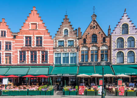 Bruges, Flanders, Belgium - June 17, 2019: Brick stone facade row with step gables, now restaurants and bars with colored awnings, on NW side of Markt Square. Menus displayed. Redactioneel