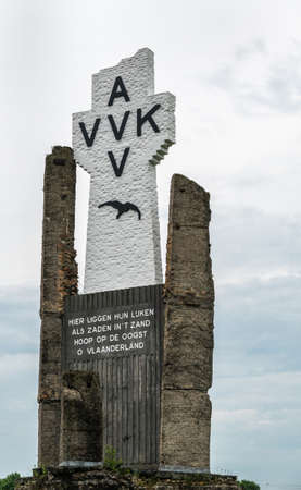 Diksmuide, Flanders, Belgium -  June 19, 2019: Closeup of Black on White Crypt memorial, remnants of dynamited tower, at site of IJzertoren, tallest peace monument of WW 1 against gray cloudscape. Editorial