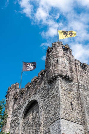 Gent, Flanders, Belgium -  June 21, 2019: Corner of Gray stone tower of Gravensteen, historic medieval castle of city against blue sky with white clouds. Flags on top,