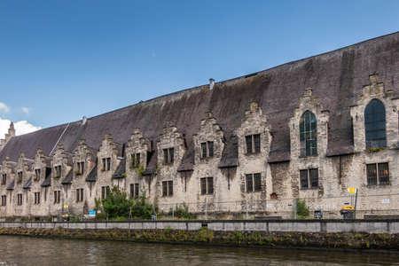 Gent, Flanders, Belgium - June 21, 2019: Closeup of historic gray-stone long facade of Vleeshuis, medieval meat trading floor, along Leie River under blue sky.