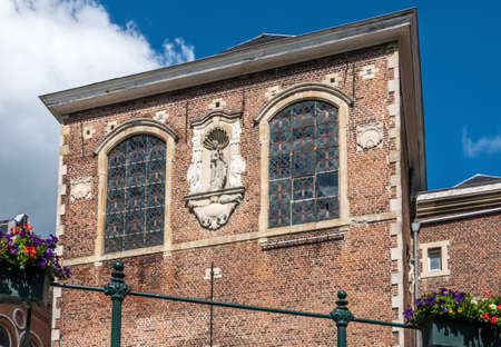 Gent, Flanders, Belgium -  June 21, 2019: Red brick facade with centrally place white Madonna statue of Saint Augustine cloister under blue sky along Lieve River. Фото со стока