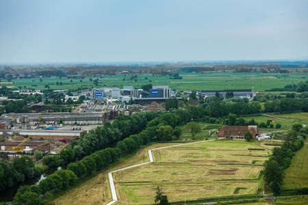Diksmuide, Flanders, Belgium -  June 19, 2019: View on farms and farm land and industrial area with Deceuninck plant from up IJzertoren, tallest peace monument of WW 1. Greens, grays and reds. Redactioneel