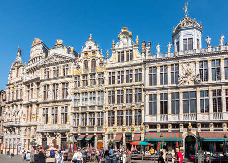 Brussels, Belgium - June 22, 2019: Beige stone facades and gables with statues on top and bar-restaurants on ground at northwest side of grand Place. People.