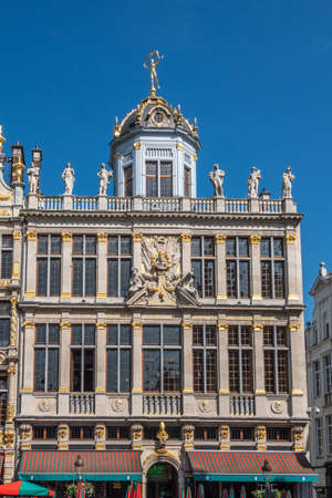 Brussels, Belgium - June 22, 2019: Beige stone facade and gable with statues on top of building named, Le Roy D'Espagne, with bar restaurant at ground, against blue sky.