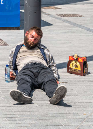 Brussels, Belgium - June 22, 2019: Filthy drunken lad sleeps in sun on gray stone Boulevard Anspach with six-pack of Leffe Abbey ale beers besides him.
