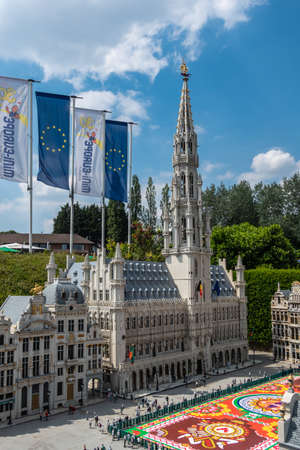 Brussels, Belgium - June 22, 2019: Mini-Europe exhibition park. Grand Place with flower carpet and City hall building with spire in miniature version against blue sky with white cloudscape. Green foliage.