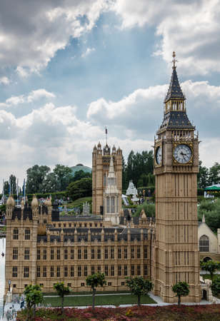 Brussels, Belgium - June 22, 2019: Mini-Europe exhibition park. London Big Ben clock tower and Parliament House built in miniature in park under blue sky with cloudscape and green foliage. Redactioneel
