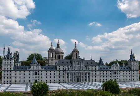 Brussels, Belgium - June 22, 2019: Mini-Europe exhibition park. Royal site of San Lorenzo de el Escorial built in miniature under blue sky with white cloudscape. Green foliage in front.