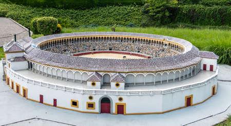 Brussels, Belgium - June 22, 2019: Mini-Europe exhibition park. Plaza de toros de la Real Maestranza de Caballeria de Seville in miniature with green foliage in back. Bull and people in the arena.