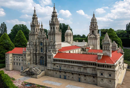 Brussels, Belgium - June 22, 2019: Mini-Europe exhibition park. Santiago de Compostela Cathedral in miniature set in green foliage environment against blue sky with white cloudscape. Brown stone and red roofs. Redactioneel