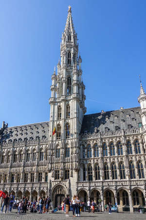 Brussels, Belgium - June 22, 2019: Grand Place with tourists and gray stone City hall building with spire amd Be;gian flag against blue sky.