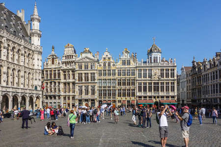 Brussels, Belgium - June 22, 2019: Grand Place with tourists and beige stone facades, gables and golden statues of northwest side against blue sky. City hall on left. Redactioneel