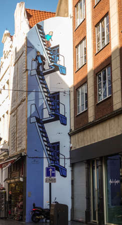 Brussels, Belgium - June 22, 2019: Tintin themed blue-white wall painting of stairway on side facade of house in Rue de l'Etuve.