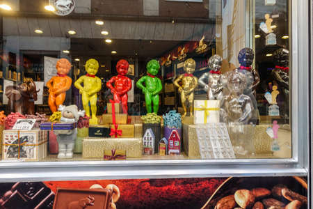 Brussels, Belgium - June 22, 2019: Large chocolate Manneken Pis statues in different colors posing on top of collection of chocolat gifts in window of confectionery store.