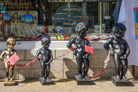 Brussels, Belgium - June 22, 2019: Closeup of chained group of metalic Manneken Pis statues in front of gift store and its display window.