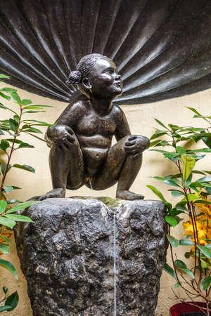 Brussels, Belgium - June 22, 2019: Closeup of iconic and original Jeanneke Pis statue, urinating on black rock.