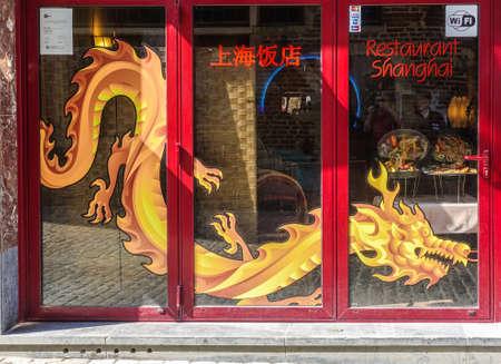 Brussels, Belgium - June 22, 2019: Closeup of red framed window with golden dragon painting of Shanghai Restaurant, Redactioneel